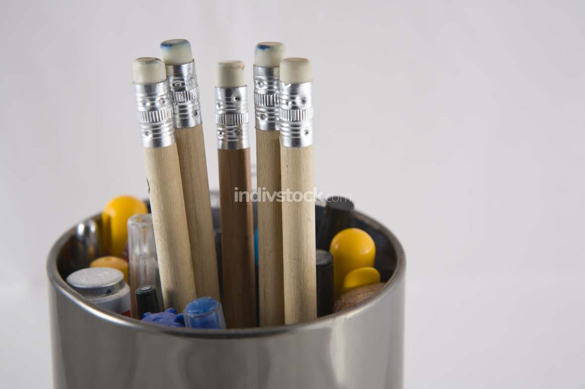 Shinny metal pencil pot with five pencils in the middle