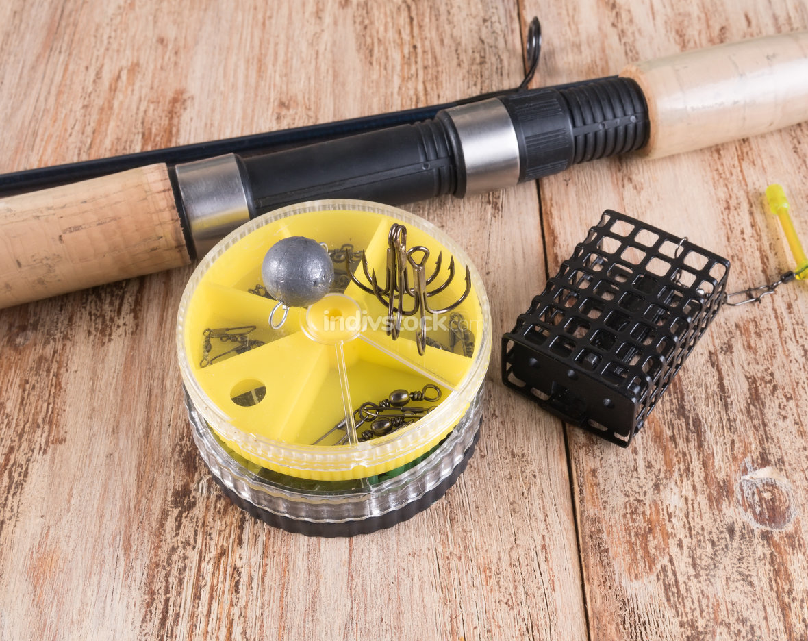 Spinning, black trough, round boxes, hooks and sinkers on wooden background