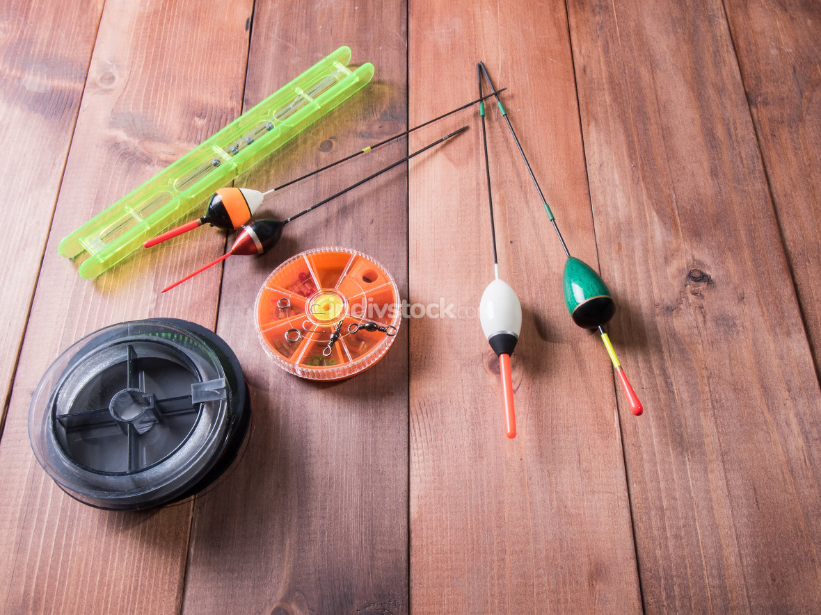 spool of fishing line, floats and a box of hooks