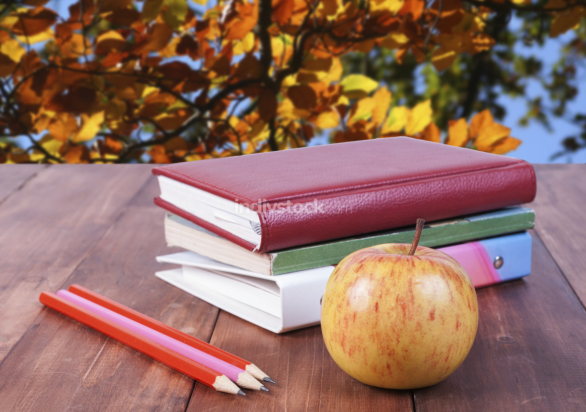 stack of books, pencils and yellow apple. Series back to school.
