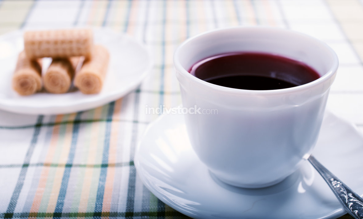 white Cup of tea hibiscus on the table and a plate of cookies