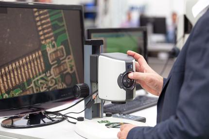 Operator working on digital microscope inspecting electronic co