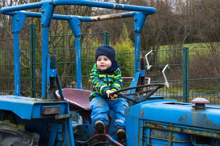 Child on the steering wheel of a tractor
