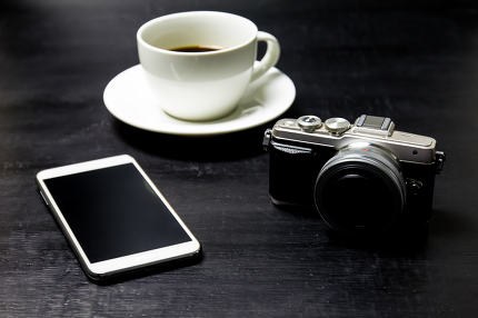 Coffee with camera and mobile phone on wood background.