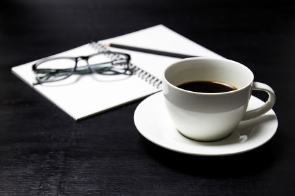 Coffee with notebook ,glasses and pencil on wood background.