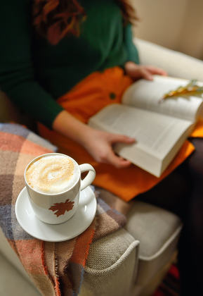 Cup of cappuccino and girl reading a book