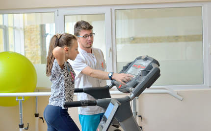 Instructor in gym with little girl