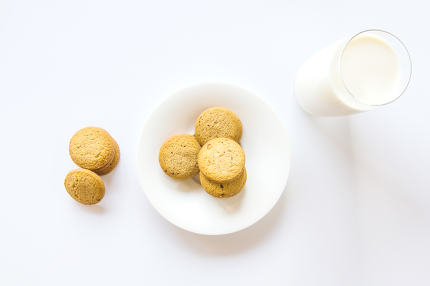 Oatmeal cookies and milk glass on white background