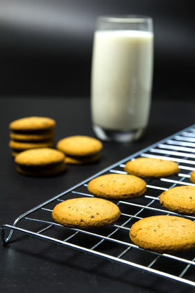 Oatmeal cookies and milk glass on wood table