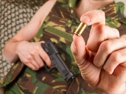 Soldier in camouflage vest is holding a gun and an empty shell