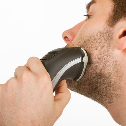 Young man shaving his beard off
