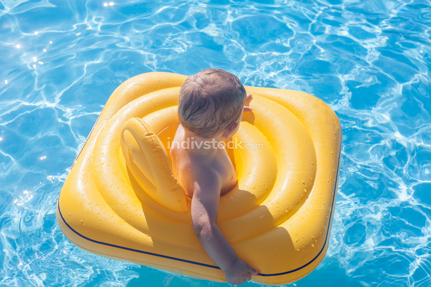 Baby boy with yellow rubber ring on swimming pool