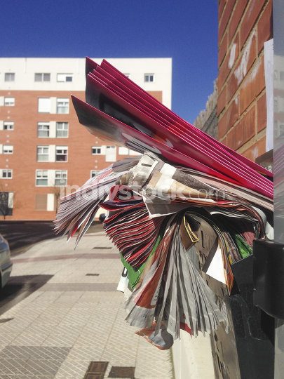 Mailbox full of junk of adverstising brochures outside apartment