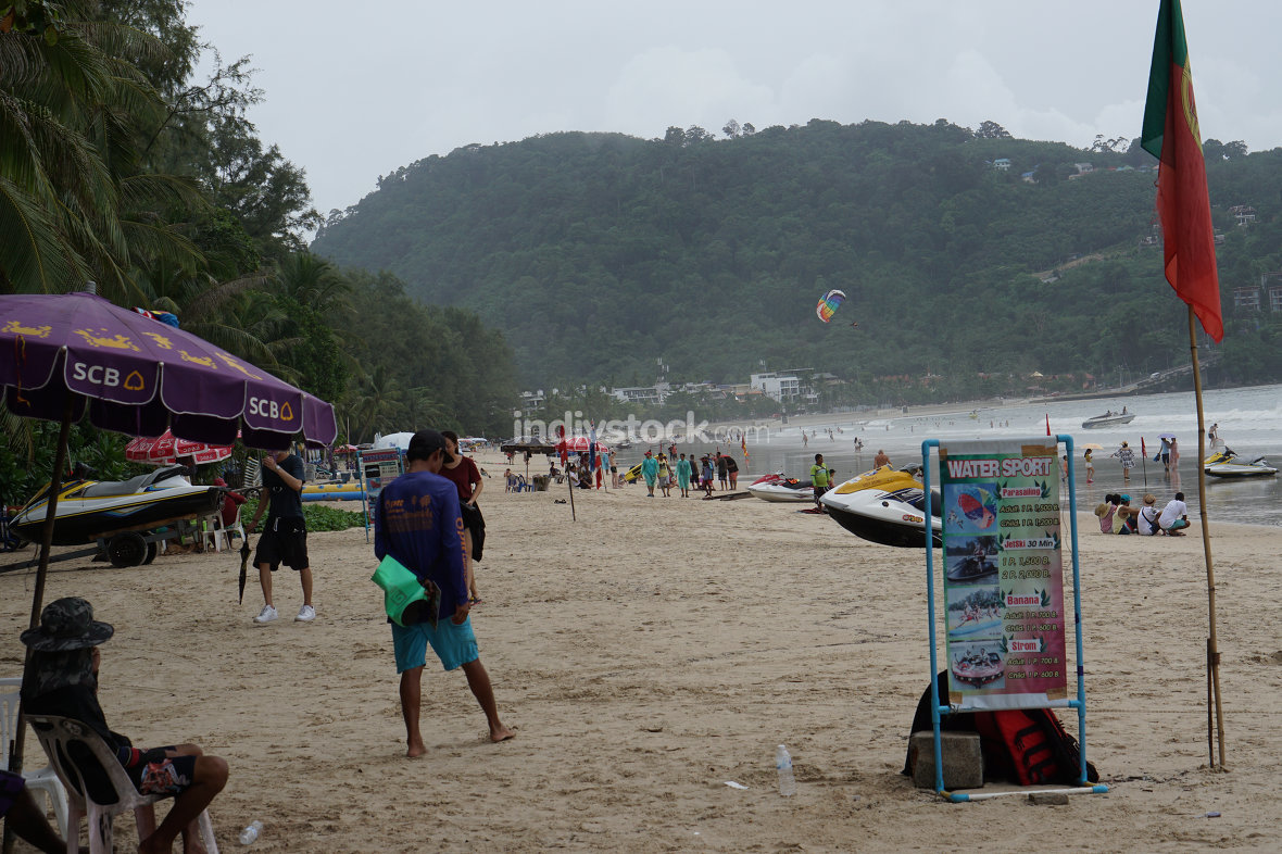 Patong beach in Phuket on a rainy dark sky day with sport activi