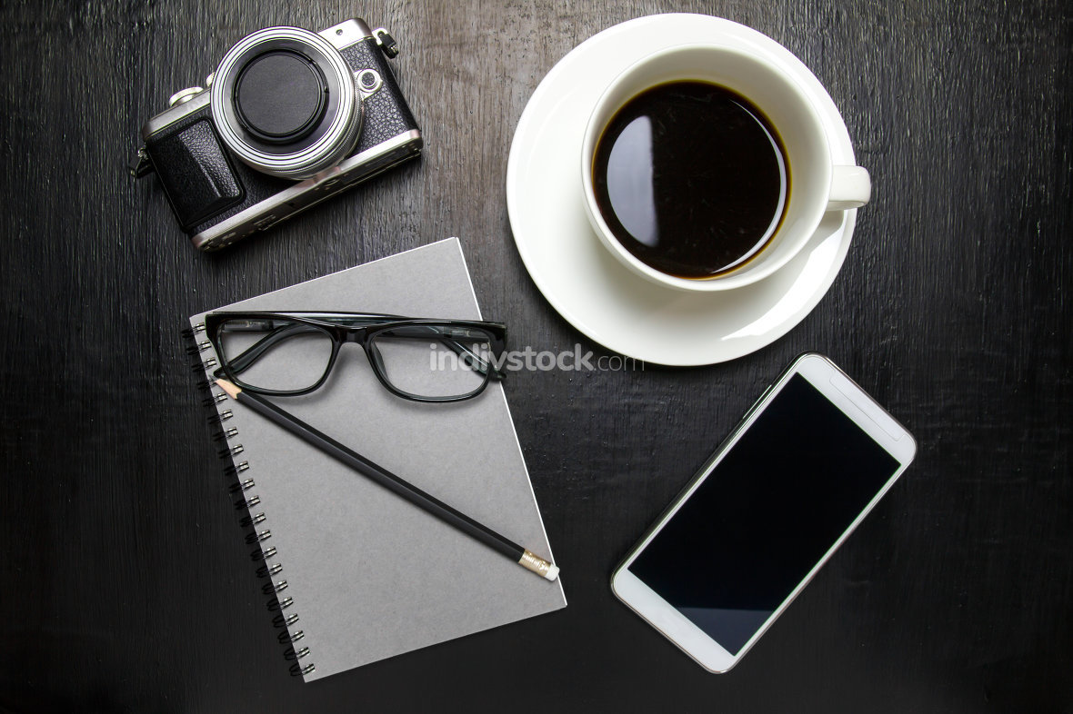 Top view of office desk workspace with coffee cup, notebook, cam