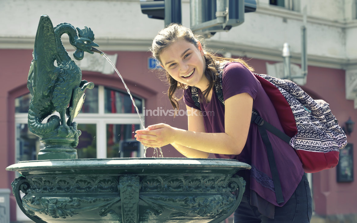 Young girl drinking  water from the fountain
