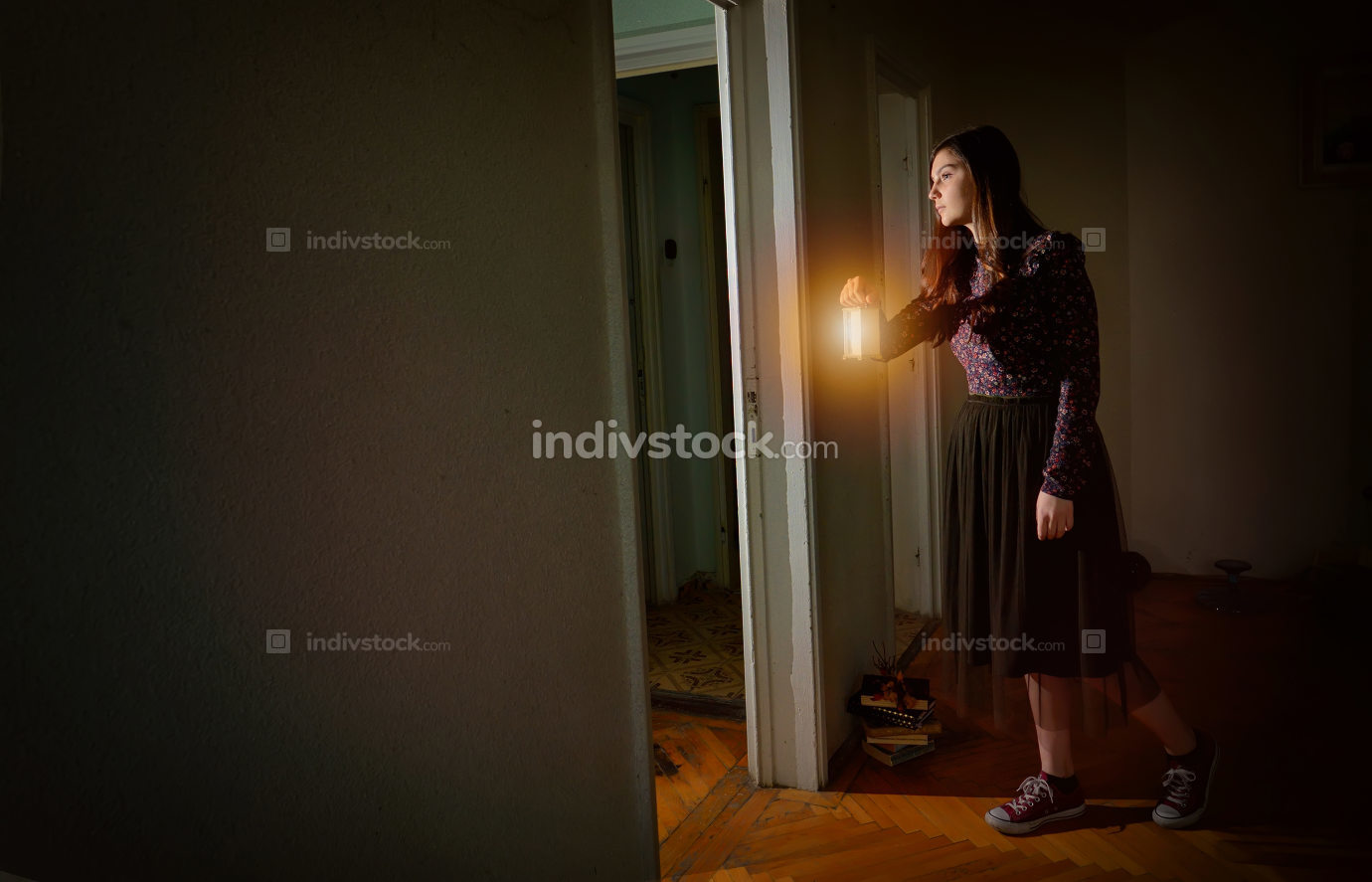 Young girl in black vintage dress with lantern