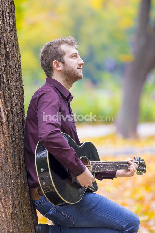 Young man sitting and playing acoustic guitar