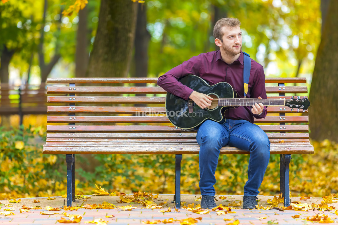 Young man sitting on bench and playing acoustic guitar