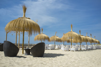 Cafe and restaurant armchairs with table and umbrella at beach