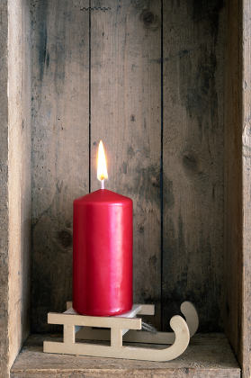 Christmas decoration red candle on a sledge in a wooden box back