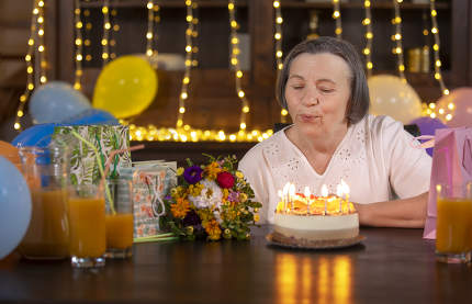 Elderly woman blowing candles at her birthday celebration