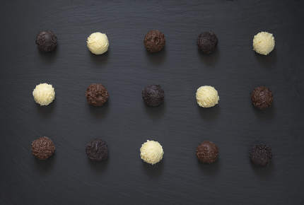 Fancy chocolate truffles ready to eat on black