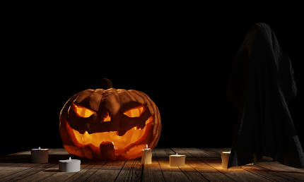 halloween pumpkin with ghost at wood planks with candle lights a