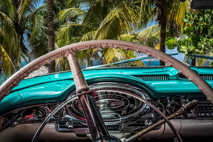 interior cockpit view of American vintage car on the beach overlooking the Caribbean Sea