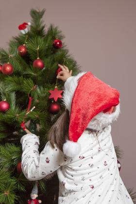 Little girl decorates Xmas Tree with red ball
