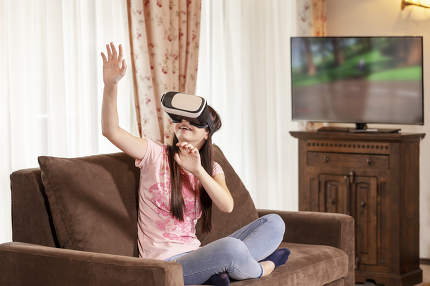 Teenager girl having fun with virtual reality glasses at home