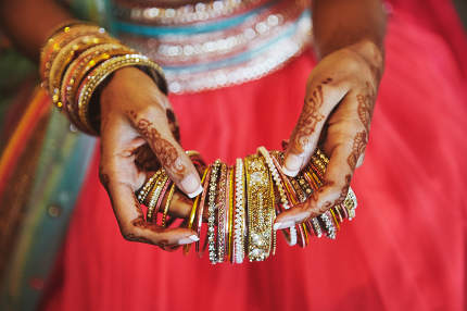 The hand with mehndi of Indian bride holding a lot of glitter br