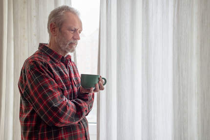 Thoughtful mature man drinking his coffee and looking out of the