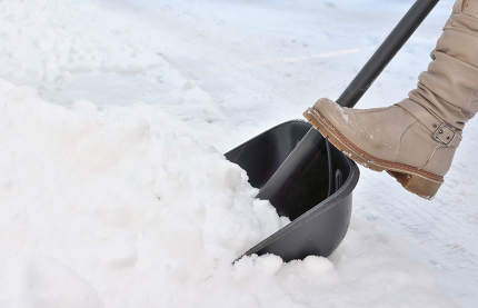 Woman Shoveling snow on street