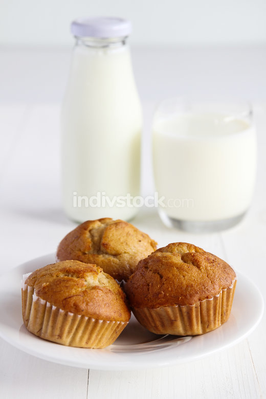 Banana cakes with milk on wooden table.