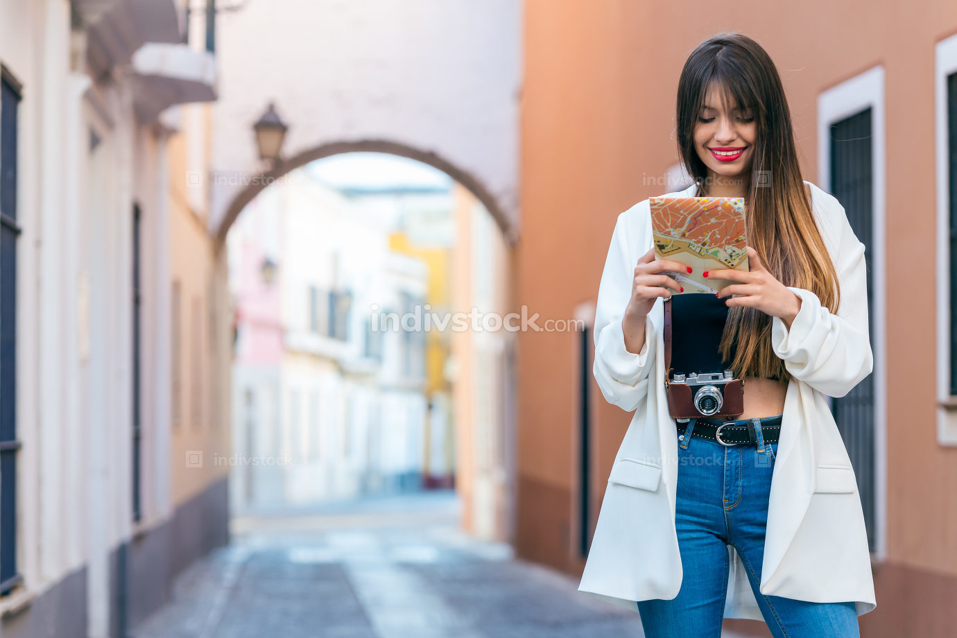 Beautiful young woman traveler with map and camera smiling.