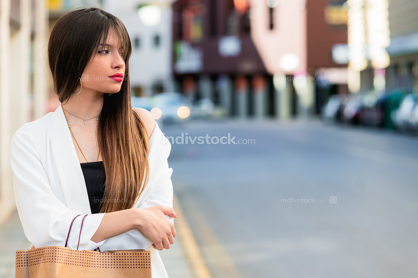 Beautiful young woman waiting in the street with copy space for
