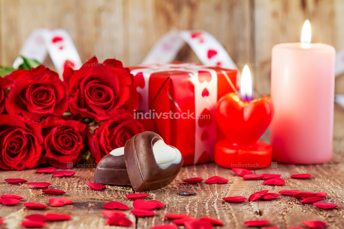 Chocolate pralines in front of bouquet of red roses