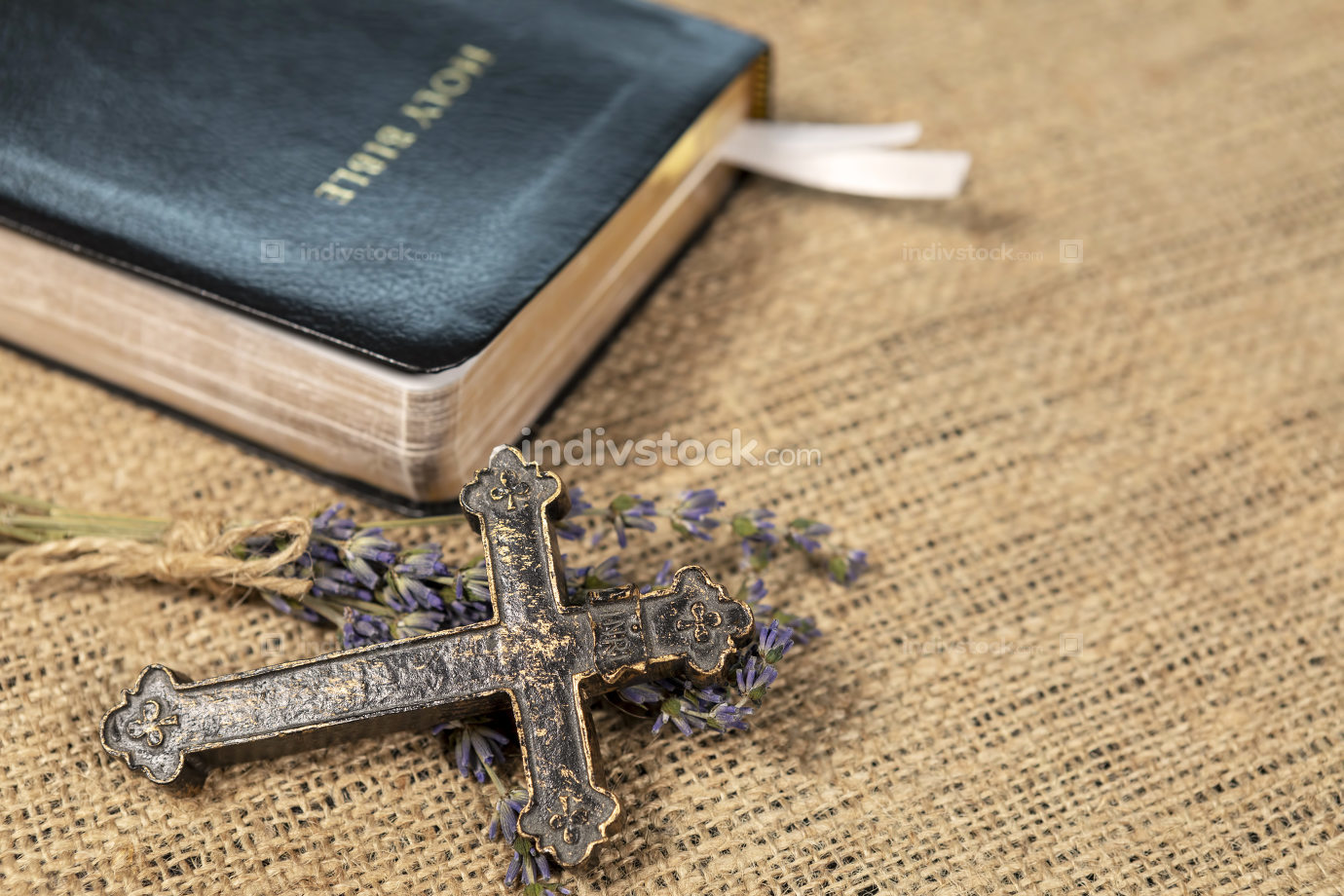 Christian cross on lavanda flowers next to Holy Bible