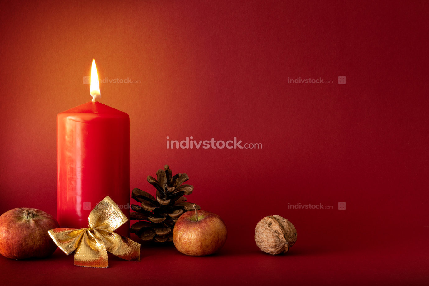 Christmas decoration with a burning candle on red background