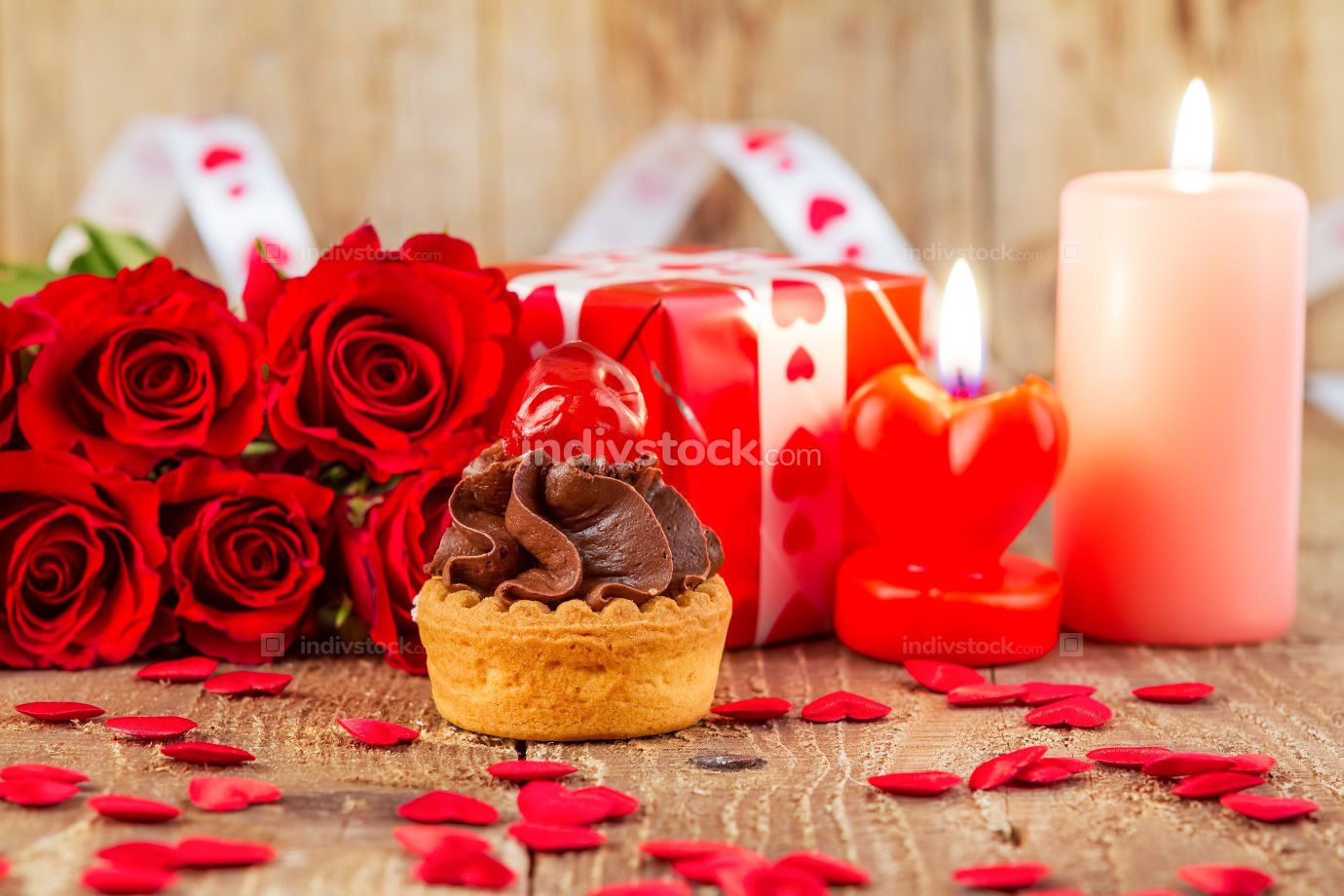 Cupcake with cherry in front of bouquet of red roses and cadles