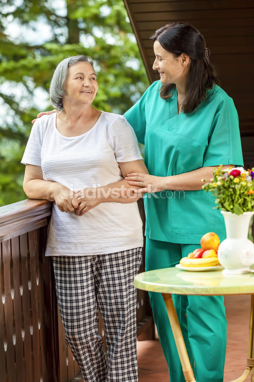 Female nurse consoling elderly woman at home