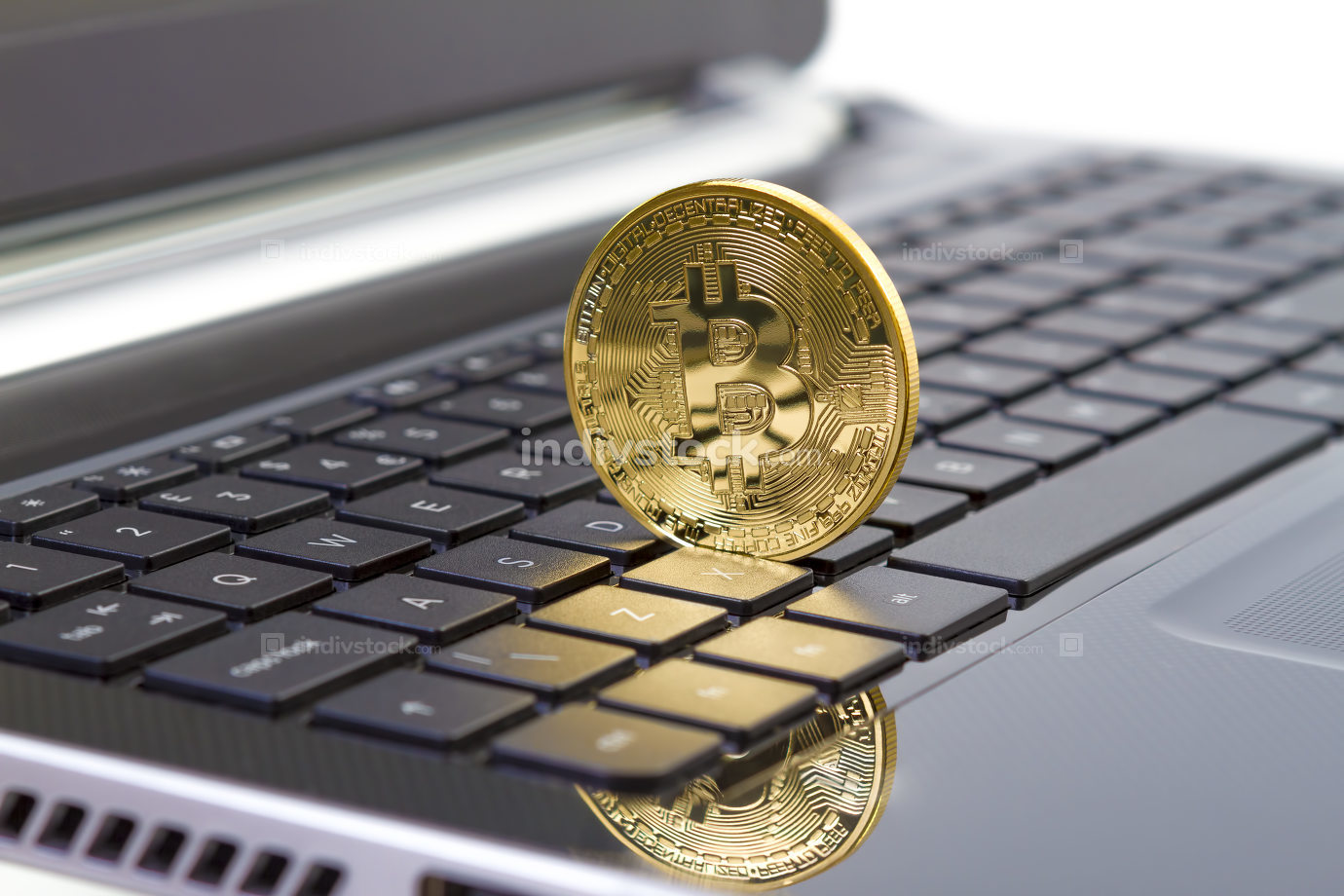 Golden bitcoin digital currency on laptop keyboard