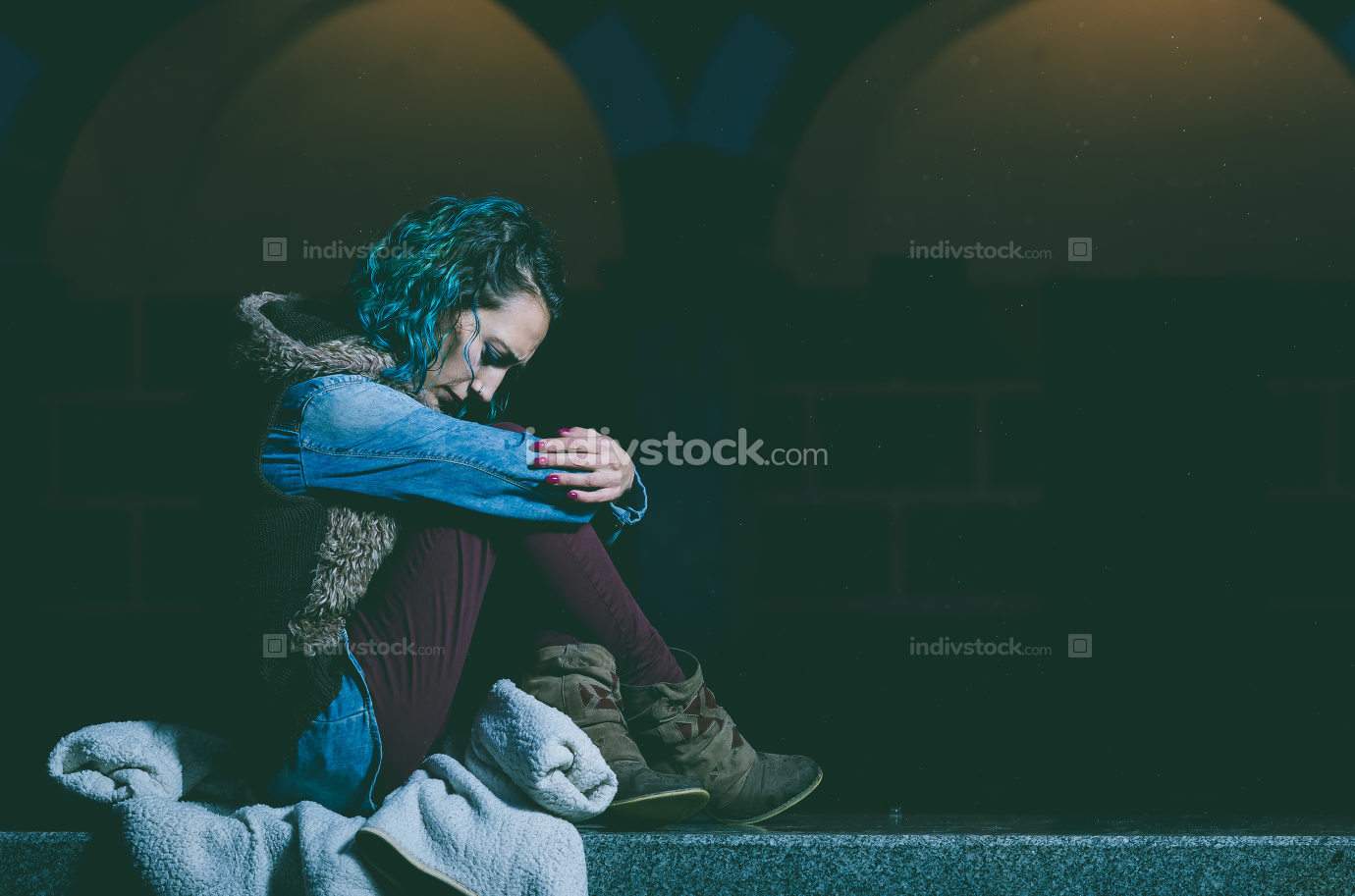 Lonely and sad girl seated sitting on a bench