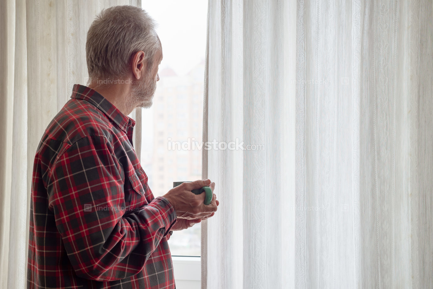 Mature man drinking his coffee and looking out of the window