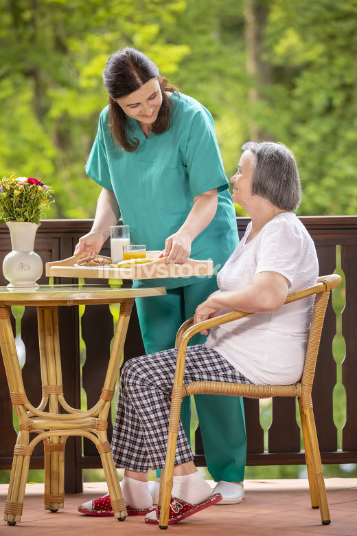 Nurse serving healthy breakfast to happy senior woman