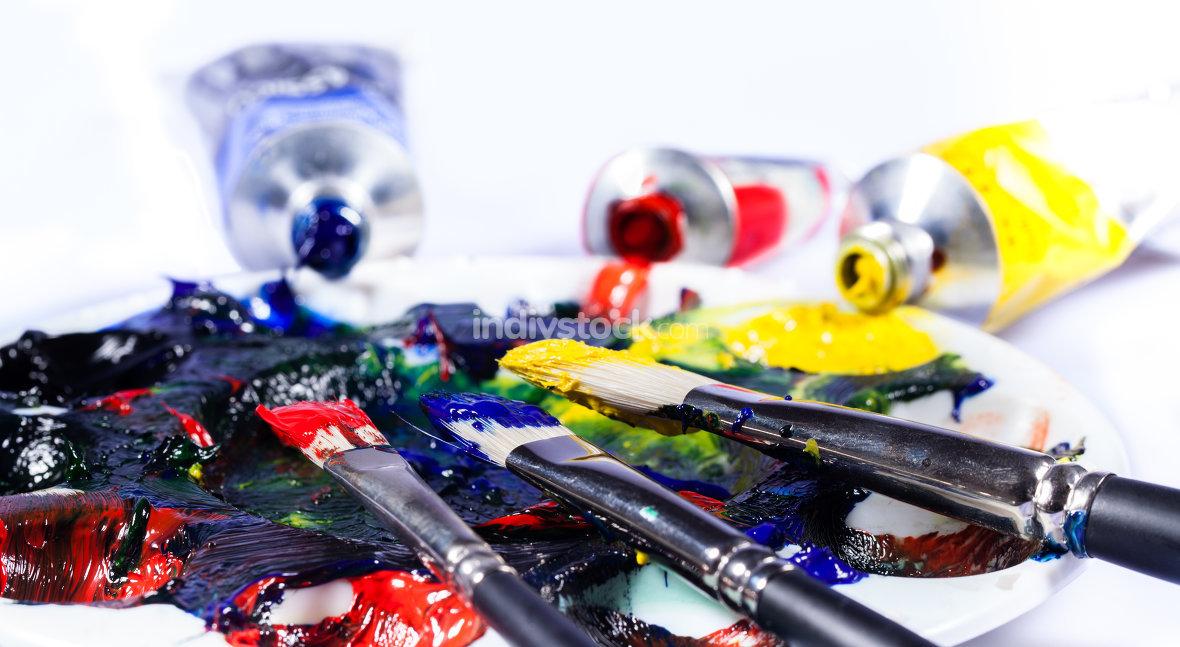 Pinsel mit Palette und Farbtuben