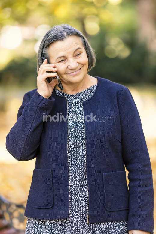 Positive senior woman talking on smartphone outdoors