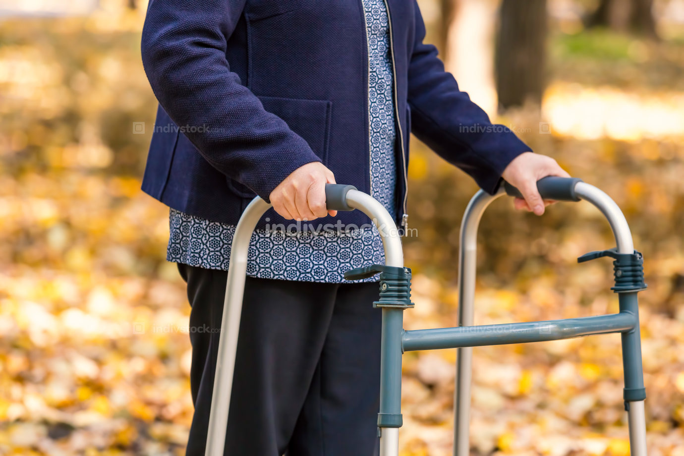 Senior woman legs walking with walker in autumn park