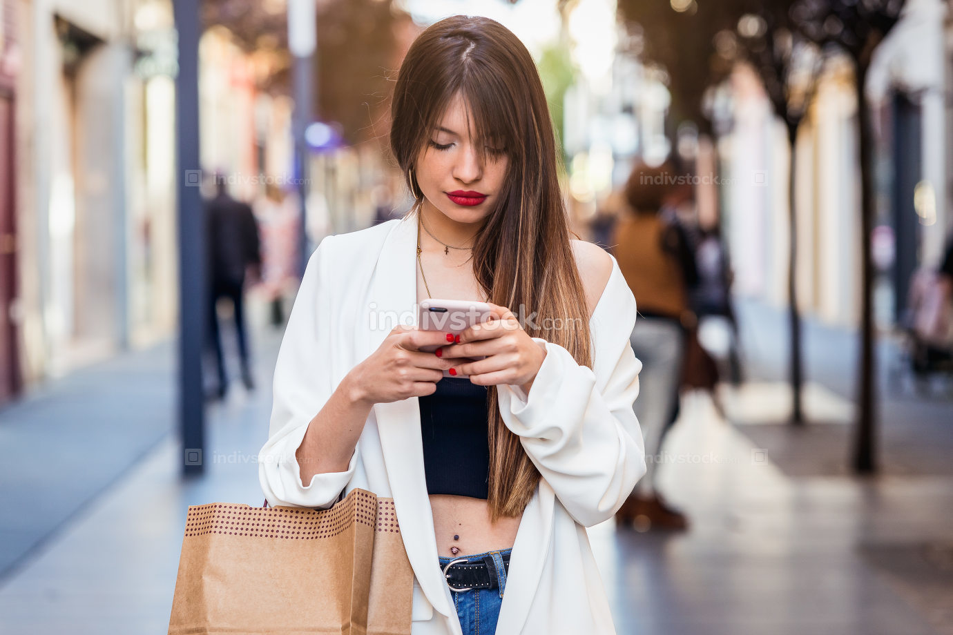 Woman buying and using mobile in commercial street